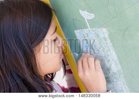 Brunette girl draws in green chalkboard with chalk