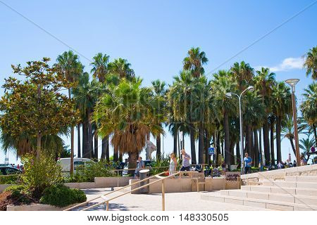 CANNES, FRANCE - 19 SEPTEMBER, 2016: Palms of Cannes, small park by the beach with people waling by
