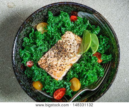 Healthy kale salad with baked salmon and cherry tomatoes on stone background. Toning. Close-up.