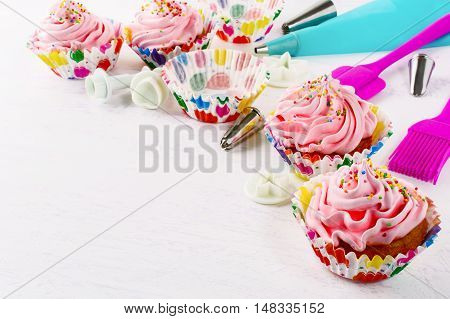 Cookware and pink birthday cupcakes. Birthday cupcake with pink whipped cream. Homemade party cupcakes.