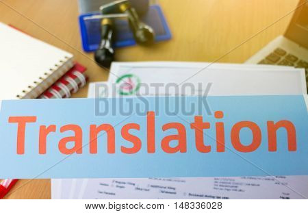 orange translation word over blur office table and paper