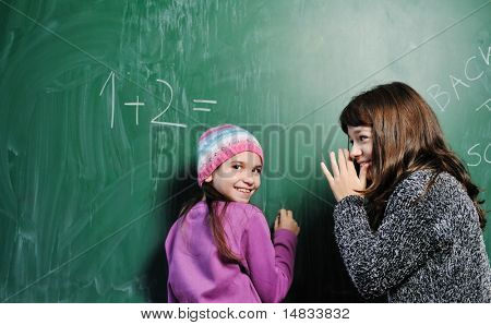happy child in school classroom solving math problem and have friend to help find solution
