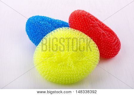 round sponges for washing dishes with different colors on a white wooden table