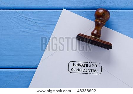 Stamp on a wooden surface and the imprint of a private and confidential.