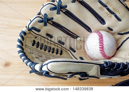 tan colored leather baseball glove and ball