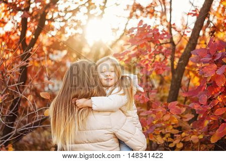 Family walk. Mother hugs daughter. Autumn Park. Sunset. Cute family relationships.