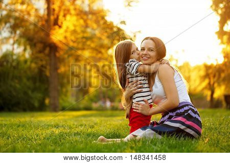 Daughter kiss her mother on the cheek. Family sits on a green lawn in the city park outdoors. Happiness of motherhood and childhood.