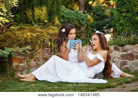 Two cute sisters reading books while sitting on the lawn. Girls discuss the reading. Literary discussion. Poetry readings. She slammed the book