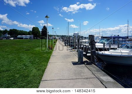 HARBOR SPRINGS, MICHIGAN / UNITED STATES - AUGUST 1, 2016: One may walk along a sidewalk adjacent to boats docked at the Harbor Springs Municipal Marina.