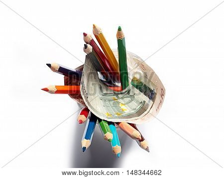 colored pencils in a glass and paper euro banknotes