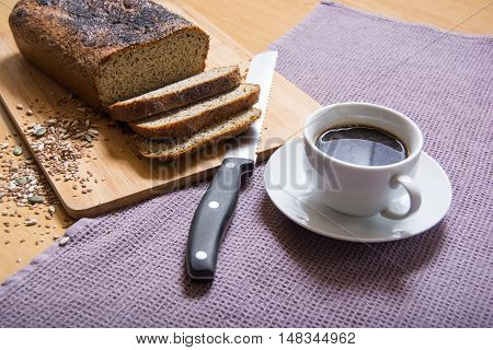 Freshly baked sliced banting seed loaf or paleo bread on a board with bread knife and cup of coffee