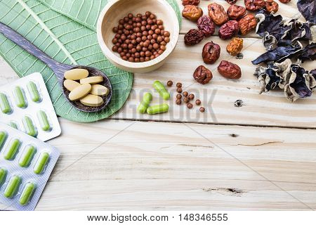 Herbal medicine herbs herbal pills tablets and blisters of capsules on wood background.