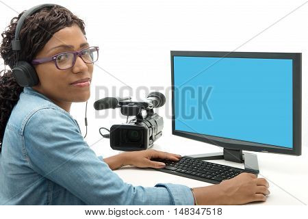 young African American woman video editor with computer and camcorder