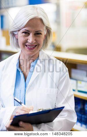 Portrait of pharmacist writing on clipboard in pharmacy