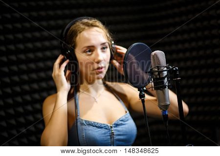 Portrait of beautiful female performer wearing headset singing song in recording studio.