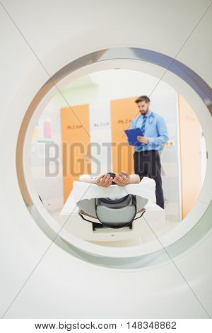 Doctor reviewing chart of patient about to have mri scan at the hospital