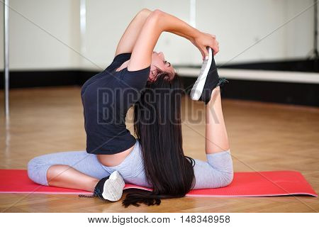 sports young girl goes in for sports in the gym. performs pole dance exercises