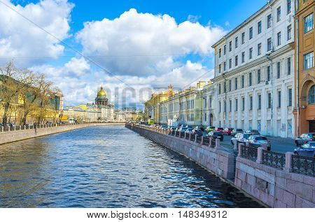The stone embankments of Moyka River with the scenic mansions and the golden dome of St Isaac's Cathedral on the background Saint Petersburg Russia.