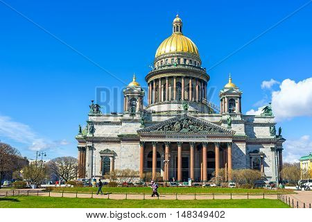 SAINT PETERSBURG RUSSIA - APRIL 25 2015: The facade of Neoclassical St Isaac's Cathedral the dome covered with pure gold numerous bronze sculptures and red granite columns decorate Basilica on April 25 in Saint Petersburg.