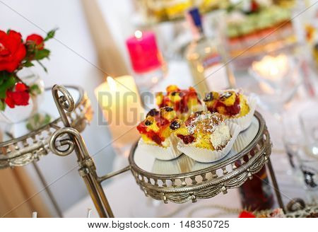 Beautifully decorated Banquet table. desserts with fruits, mousse, biscuits