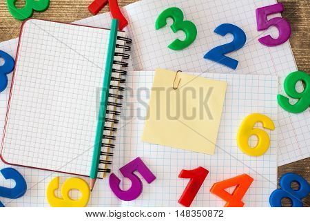 Squared exercise bookpersonal organizercolored numbers and blank sticky note