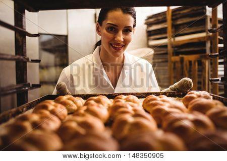 Portrait of female baker holding a tray of michetta in bakery shop