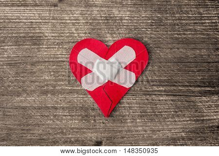 Broken heart with plaster on the old wooden background