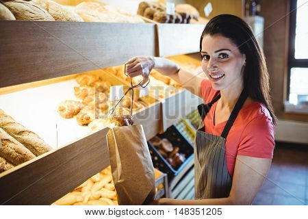 Female baker packing sweet food in bakery shop