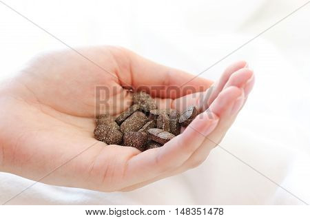 Pills in a female hand. A handful of pills on a white background