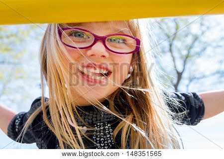 Close up image of an excited blond girl with blue eyes and pink glasses. She is climbing yellow playground equipment.