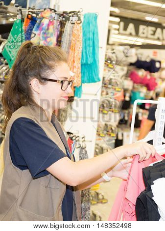 Woman choosing dress during shopping at garments apparel clothing shop