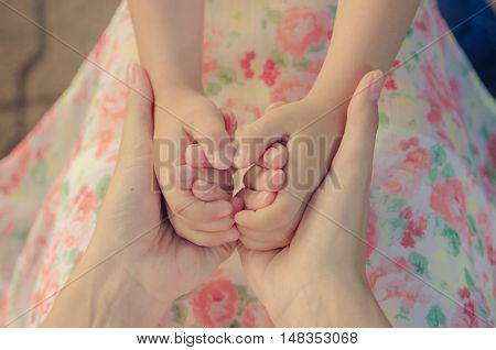 Children's palms in female palms. Mother and child (vintage)