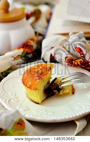 Muffin cottage cheese with chocolate inside, on a plate on a light and airy tablecloths on background of an open book and sugar