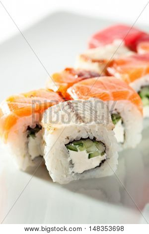 Rainbow Maki Sushi - Roll with Cucumber and Cream Cheese inside. Tuna, Salmon and Eel outside