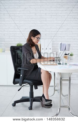 Busyness lady working in office at her table