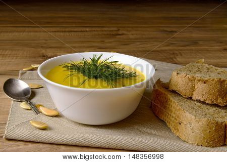 Bowl of pumpkin soup with bread and greens on a wooden surface