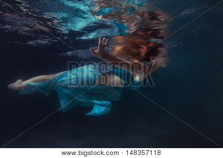 Woman in a dress swims under water her hair develop in water.