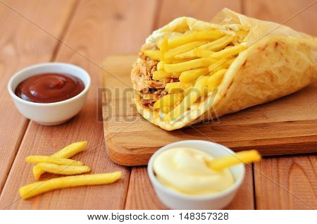 Gyro with fries and two sauces on wooden background