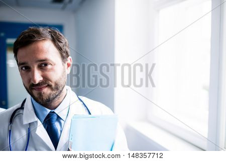 Portrait of a confident doctor with clipboard standing in the hospital corridor