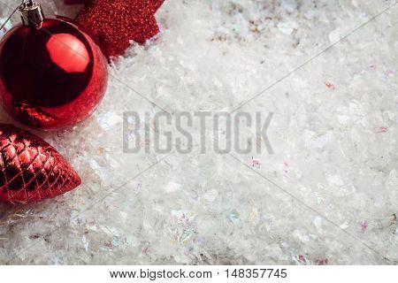 Overhead view of red baubles in fake snow