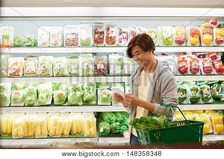 Young man reading grocery list when shopping in supermarket