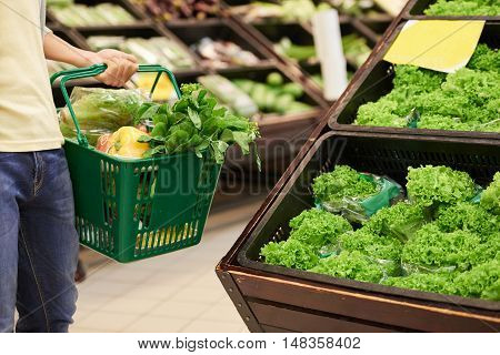 Cropped image of guy shopping for greens in supermarket