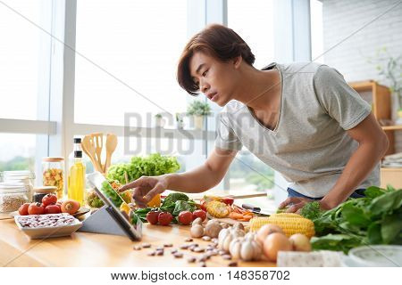 Vietnamese young man following recipe on tablet when cooking