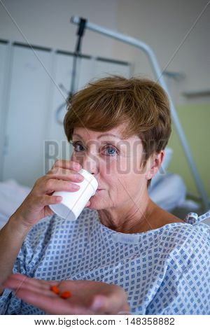 Portrait of patient taking medication in hospital room