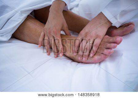 Doctor giving foot treatment to patient in hospital room