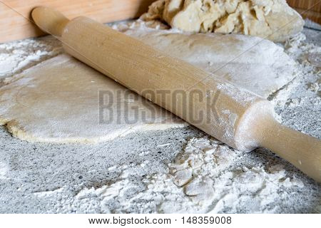 Dough for pizza bread gingerbread and rolling-pin on table