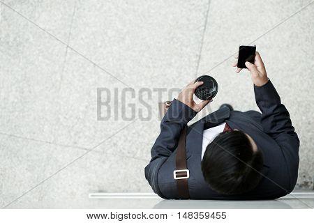 Businessman enjoying coffee and reading news on smartphone