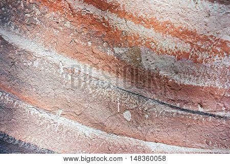diagonal brown white and black strips on a concrete wall