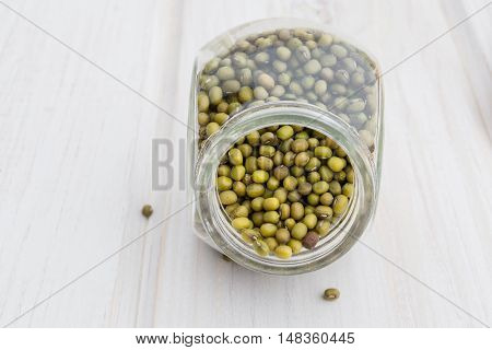 Sprouted mung beans in a glass jar on a white wooden background