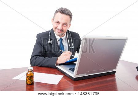 Male Medic At Office Smiling And Writing On Clipboard